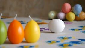 Semana Santa Huevo blanco de la vuelta femenina de la mano en la tabla Huevos de Pascua coloridos en el fondo