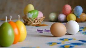 Semana Santa la mano masculina da vuelta a un huevo marrón del pollo en la tabla huevos de Pascua olorful en el fondo
