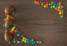 Semana Santa Los huevos de chocolate con los caramelos multicolores mienten en una tabla marr?n de madera fotos de archivo