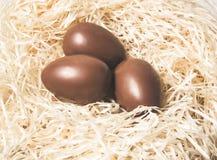 Semana Santa Los huevos de chocolate mienten en una jerarqu?a en una tabla blanca de madera imagenes de archivo