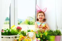 Semana Santa muchacha feliz del niño con los oídos del conejito y sitti colorido de los huevos fotografía de archivo