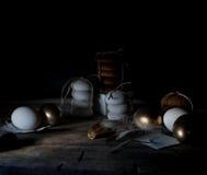 Semana Santa Noche de Pascua Huevos y tortas de oro en una tabla de madera Plumas blancas vendimia Fondo oscuro Imágenes de archivo libres de regalías