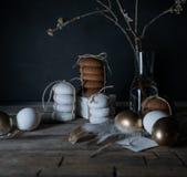 Semana Santa Noche de Pascua Huevos y tortas de oro en una tabla de madera Plumas blancas vendimia Fondo oscuro Fotografía de archivo