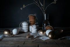 Semana Santa Noche de Pascua Huevos y tortas de oro en una tabla de madera Plumas blancas vendimia Fondo oscuro Foto de archivo