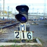 Semaphore with burning blue light. The intersection of railway tracks. Railway semaphore traffic light against the background of a day railway landscape. Signal stock photos