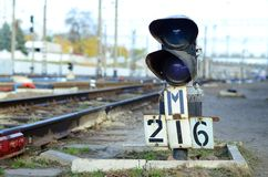 Semaphore with burning blue light. The intersection of railway tracks. Railway semaphore traffic light against the background of a day railway landscape. Signal royalty free stock images