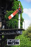 Semaphore railway signal and platform sign, Hampton Loade,. Semaphore signal of the bracket design showing the lower quadrant home all clear at the railway stock images