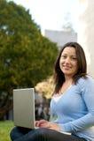 Sembrare allievo femminile con il computer portatile sulla città universitaria Fotografia Stock Libera da Diritti