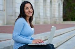 Sembrare allievo femminile con il computer portatile sulla scala della città universitaria Fotografie Stock Libere da Diritti
