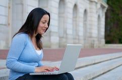 Sembrare allievo femminile con il computer portatile sulla scala della città universitaria Fotografia Stock