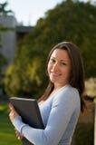 Sembrare allievo femminile con il manuale sulla città universitaria Immagine Stock
