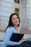 Sembrare allievo femminile con il manuale sulla città universitaria Immagine Stock Libera da Diritti