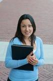 Sembrare allievo femminile con il manuale sulla città universitaria Fotografia Stock