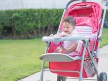 Sembrare asiatico del bambino felice in passeggiatore in parco Fotografia Stock Libera da Diritti