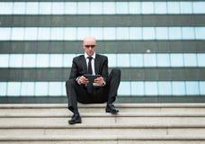 Sembrare dell'uomo di affari sicuro facendo uso della compressa del computer Fotografia Stock