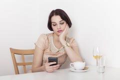 Sembrare della donna deludenti al suo telefono cellulare Fotografie Stock