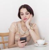 Sembrare della donna deludenti al suo telefono cellulare Fotografia Stock Libera da Diritti