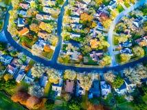 Sembrare il basso diritto sopra la Comunità moderna della casa del sobborgo con la caduta colora Streetes curvo Fotografie Stock Libere da Diritti