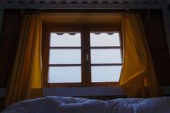 Sembrare mattina nebbiosa di inverno dalle montagne delle tende di finestra del letto Fotografie Stock