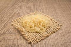 Seme cinese scottato del riso Grani su ritaglio quadrato di iuta wo Immagine Stock