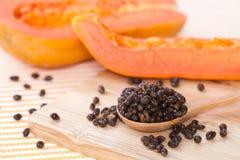 Seme della papaia gialla sul cucchiaio e sul blocco di legno con la papaia gialla sopra dietro Fotografia Stock Libera da Diritti