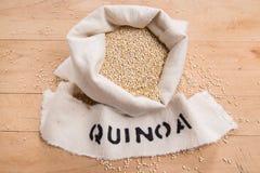 Seme della quinoa in una borsa crema del tessuto su un fondo di legno sollecitato Fotografie Stock