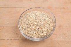Seme della quinoa in una ciotola di vetro su un fondo di legno sollecitato Fotografie Stock