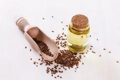 Seme di lino e olio di semi di lino sopra fondo bianco fotografia stock