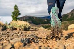 Semelle de chaussure marchant en montagnes sur le sentier piéton rocheux photos stock