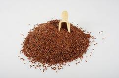 Semence d'oeillette avec une cuillère en bois Photographie stock libre de droits