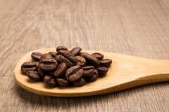 Semente dos feijões de café Grões na colher de madeira rustic fotos de stock royalty free