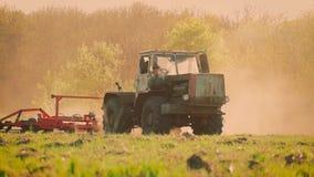 Sementeira do trator agrícola e campo da cultura Trator que trabalha no campo no por do sol vídeos de arquivo