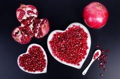 Sementes da romã em uma forma de um coração no fundo de madeira fotos de stock