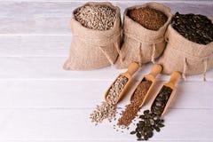 Sementes de abóbora, girassol e sementes de linho na colher de madeira No saco da juta do fundo com sementes Foto de Stock