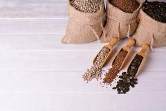 Sementes de abóbora, girassol e sementes de linho na colher de madeira No saco da juta do fundo com sementes Fotografia de Stock