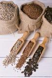 Sementes de abóbora, girassol e sementes de linho na colher de madeira No saco da juta do fundo com sementes Imagens de Stock