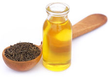 Sementes de alcaravia com óleo essencial na garrafa de vidro Imagem de Stock Royalty Free