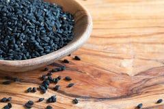 Sementes de cominhos pretas em uma colher de madeira com espaço da cópia foto de stock royalty free