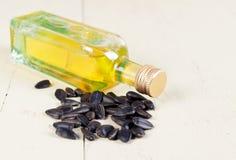 Sementes de girassol e uma garrafa do óleo no fundo de madeira Foto de Stock