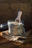 Sementes de sésamo brancas em um recipiente de vidro com uma colher de madeira Fotografia de Stock Royalty Free