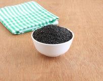 Sementes de sésamo pretas do alimento saudável em uma bacia imagem de stock