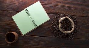 Sementes do café, um copo do caderno em um fundo de madeira imagens de stock