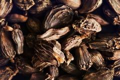Sementes pretas do cardamomo na bacia de madeira Ingre aromático, tradicional Imagem de Stock