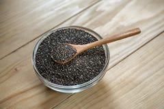 Sementes pretas orgânicas cruas do chia na colher de madeira foto de stock