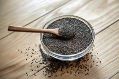 Sementes pretas orgânicas cruas do chia na colher de madeira fotos de stock royalty free