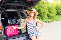 Semester-, loppbegrepp - ung kvinna som är klar för resan på sommarferier med resväskor och bil Arkivbild