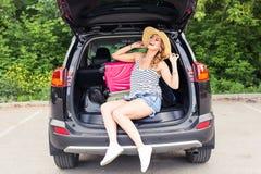 Semester-, loppbegrepp - ung kvinna som är klar för resan på sommarferier med resväskor och bil Royaltyfri Fotografi
