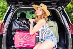 Semester-, loppbegrepp - ung kvinna som är klar för resan på sommarferier med resväskor och bil Royaltyfri Bild