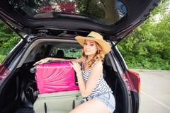 Semester-, loppbegrepp - ung kvinna som är klar för resan på sommarferier med resväskor och bil Fotografering för Bildbyråer