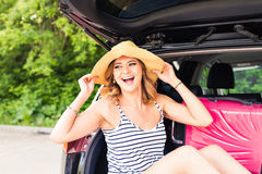 Semester-, loppbegrepp - ung kvinna som är klar för resan på sommarferier med resväskor och bil Arkivfoto